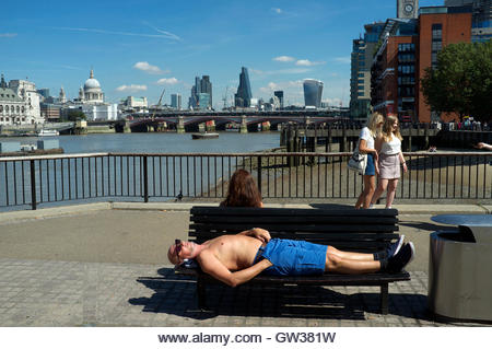 Sunbathing man on a bench seat, on Queen's Walk, Southbank, London, UK. - Stock Image
