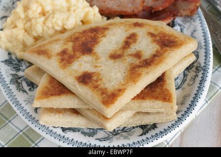 Irish potato farls or potato cakes with bacon and scrambled eggs - Stock Image