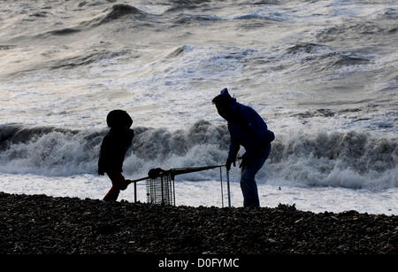 Brighton Sussex UK 25 November 2012 - An adult and child struggle to clear a  supermarket trolley off the beach - Stock Image