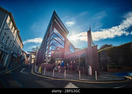 Dramatic backlit photograph of the Wexford Town Library in Wexford Ireland on a sunny day with blue shy with clouds - Stock Image