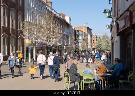 People drinking coffee outside on a spring day on Worcester High Street, England - Stock Image
