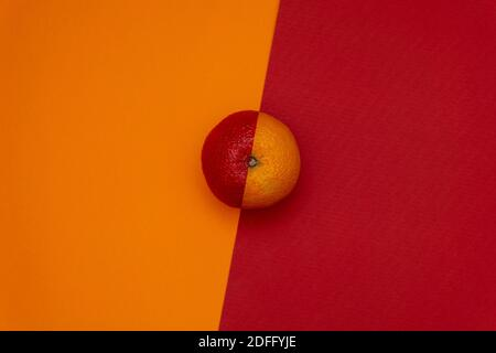 Half red orange on dual tone background. Flat lay. Minimal food concept - Stock Image