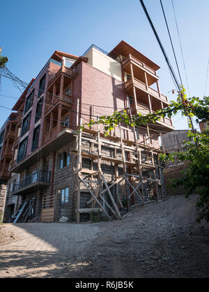 Improvised, rickety scaffolding up the side of a house during building work in the suburbs above the Abanotubani area of Tbilisi, Georgia. - Stock Image