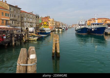 Chioggia, Italy (30th October 2020) - The San Domenico water channel with some big fishing boats and typical houses on the shore - Stock Image