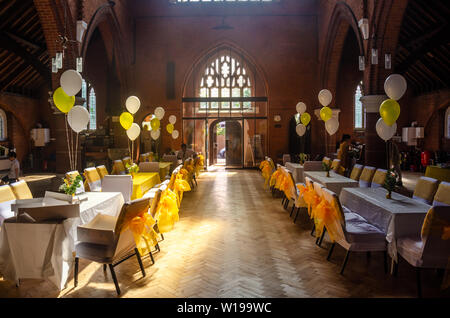 A church hall laid out with tables and chairs dressed in white fabric with yellow ribbon bows ready for a party or reception. - Stock Image