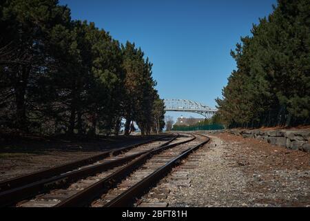 Photograph looking down left curving railroad tracks toward the US Canadian international crossing Blue Water Bridge in Port Huron Michigan USA - Stock Image