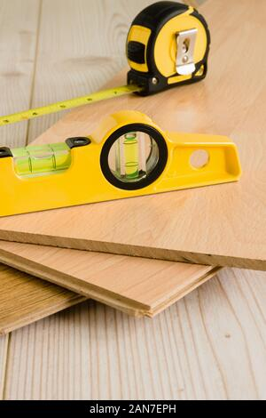 Pieces of wood laminate flooring ready to be laid with a carpenters spirit level - Stock Image