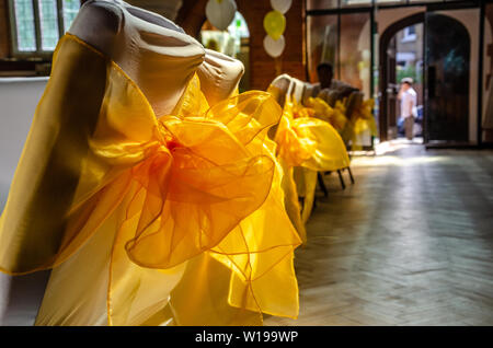 Chairs at a reception in a hall dressed with white fabric and decorated with yellow ribbon bows. - Stock Image