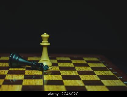 chess piece, white queen beats black king, on board - Stock Image
