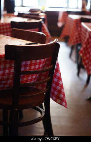 Empty restaurant tables with red check table cloths in an American restaurant - Stock Image
