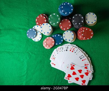 casino chips, of different colors, with a deck of cards, to play poker on a green table. - Stock Image