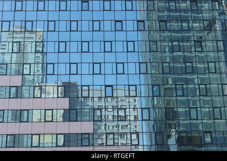 Warsaw, reflection of block towers in the windows of a modern building - Stock Image