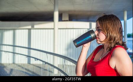 Young woman, with short hair and a red T-shirt, drinks coffee with a dark thermos, leaning on a railing - Stock Image