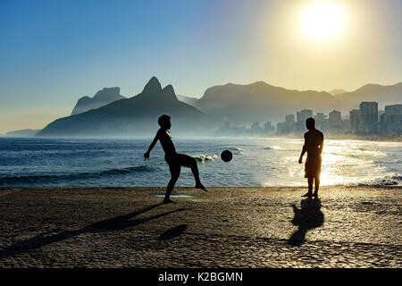 Boy playing soccer in front of the sea during sunset - Stock Image