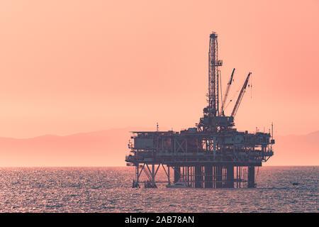 An oil rig far in the distance on the ocean - Stock Image