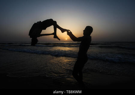Gaza City, Gaza Strip, Palestinian Territory. 30th May, 2019. A Palestinian youth plays parkour on the beach of the Mediterranean sea during the sunset, in Gaza city on May 30, 2019 Credit: Mahmoud Ajjour/APA Images/ZUMA Wire/Alamy Live News - Stock Image