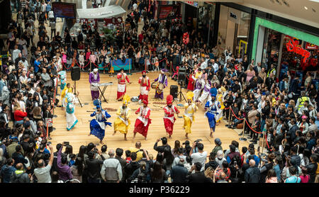 The Lions of Punjab, a Bhangra dancing troupe, perform an energetic routine to an appreciative audience in Birmingham's Bullring Shopping Centre. - Stock Image
