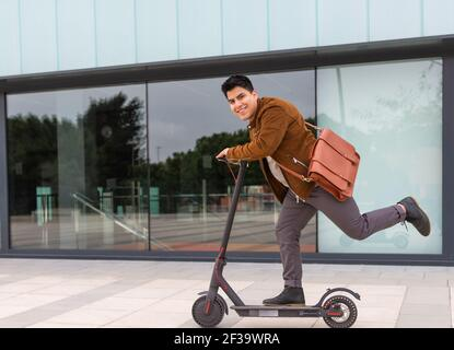 young boy with a brown briefcase driving the electric scooter with one leg - Stock Image