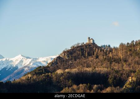 The ancient church of San Floriano (St. Florian) of the 10th century  as seen from the alpine village of Illegio, in northern Italy - Stock Image