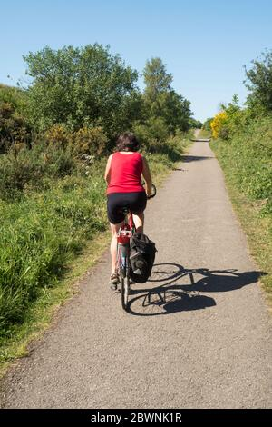 Mature woman cycling along the C2C path between Sunderland and Consett, England, UK - Stock Image