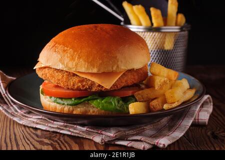 Chicken fillet in a in a brioche bun with lettuce tomatoes and cheese and skin on fries shot with creative lighting - Stock Image