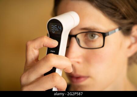 A young woman in her thirties diagnosing whether she has a fever by taking her own temperature with a digital infrared thermometer. UK - Stock Image
