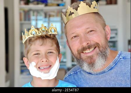 Father and son put the crown on their heads and have fun. Father has a beard. Son made a beard out of shaving foam - Stock Image