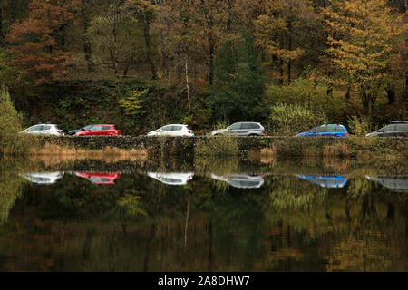 Parked cars reflected in Yew tree tarn in the English Lake district, UK. - Stock Image