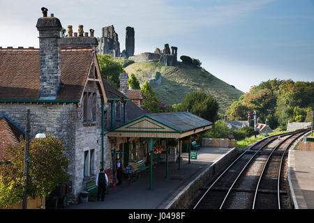 Corffe Castle Train Station and the ruins of the castle in the distance during late afternoon summer sunshine - Stock Image