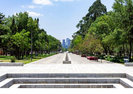 Looking down Chapultepec Park's Paseo de los Compositores toward Mexico City's Polanco neighborhood. The Fuente Xochipilli is visible on the left. - Stock Image