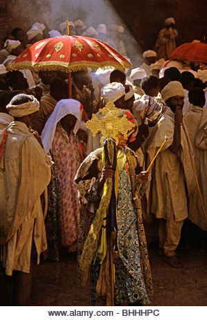 Deacon carries processional cross during 'Genna' (Christmas) celebrations - Stock Image