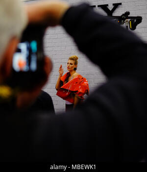 Photographers compete & jostle to take photos of a beautiful female model on a stand at the Photography Show at the NEC Birmingham in March 2018 - Stock Image