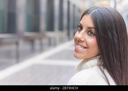 Modern and smiling young girl posing on the street - Stock Image