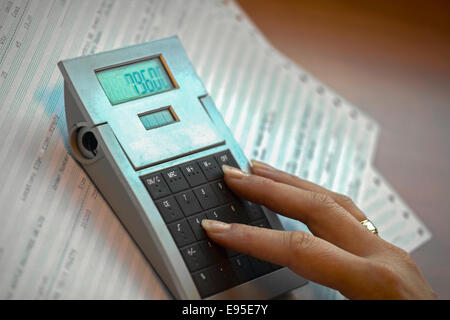 Woman working with a calculator - Stock Image
