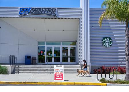Woman walking dog in front of Epicenter sports and entertainment multi-business complex in Santa Rosa, California, USA. - Stock Image