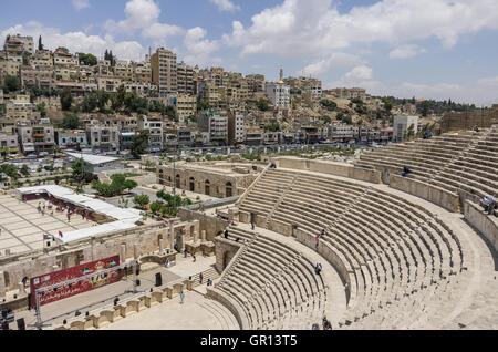 Amman, Jordan -May 28, 2016: Roman amphitheatre in downtown with Amman cityscape at background - Stock Image