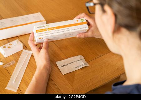 A woman taking a self diagnostic VivaDiag SARS-CoV-2 Ag Rapid Test for Covid-19 at home - Stock Image