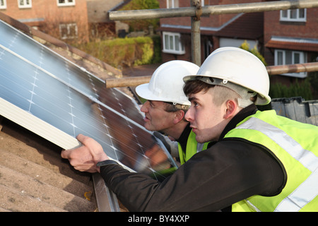 Installing photo voltaic solar panels onto the roof of a domestic house within Washington, North East England, UK - Stock Image