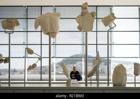 A tourist views the west pediment of the Parthenon in the Acropolis Museum in Athens, Greece - Stock Image