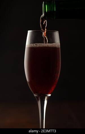 A glass of red wine with red wine bottle for celebrating party during New year evening - Stock Image