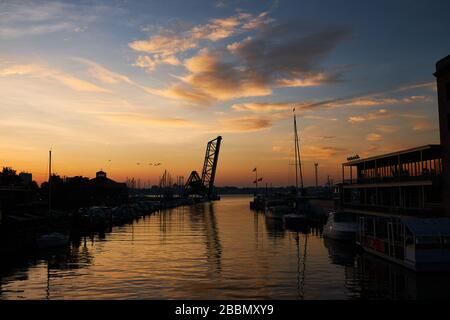Beautiful sunrise over the Black River downtown Port huron, Michigan with view of city marina and train bridge. - Stock Image