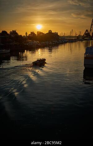 Single boat at sunrise traveling Black River in Port Huron, MI to St. Clair River and Lake Huron. - Stock Image