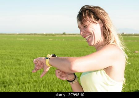 A young sportswoman girl happily checks the statistics on her watch after practicing running on the field - Stock Image