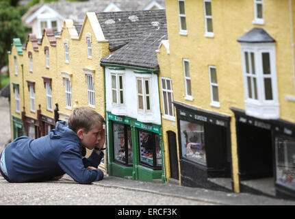 A boy looks like a giant as he looks through a shop window during a visit to The Model Village in Godshill on the - Stock Image