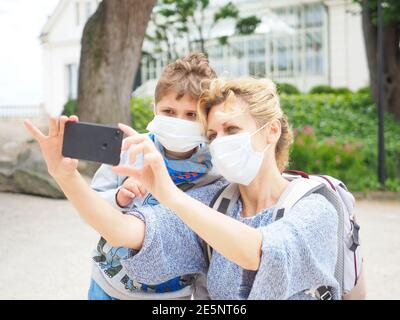 Mother with her son in face mask are travelling and taking a picture. Mother and child wear facemask during coronavirus or flu outbreak. - Stock Image