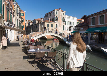 A female tourist looking at tourists and residents on the streets Fondamenta Minotto & Fondamenta del Gaffaro in the Santa Croce area of Venice, Italy - Stock Image
