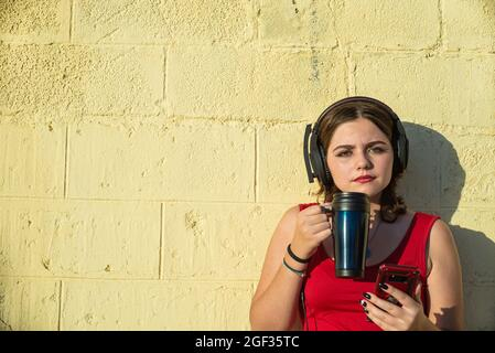 short-haired young woman, looks at camera, while holding a smartphone, drinking coffee, and listening to music on a yellow wall background, giving it - Stock Image