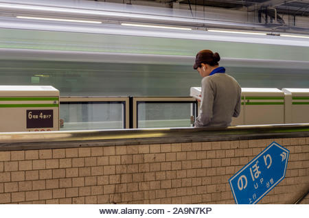 A woman reads trackside while waiting on a Yamanote Line train at Tokyo's Ikebukuro Station. - Stock Image
