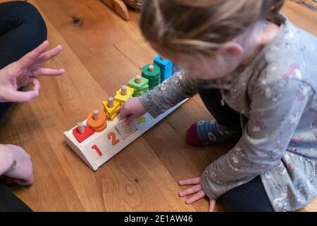 A mother holding up her fingers to show her two year old daughter which number to place, using a counting shapes stacker educational toy - Stock Image