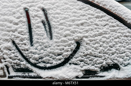 Snow background. Texture of wet snow with a cheerful smiley symbol pattern in the winter window of the car outdoors - Stock Image